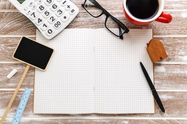 Cuaderno en blanco con signo de venta y calculadora