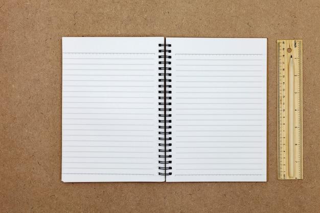 Cuaderno en blanco sobre fondo de papel marrón