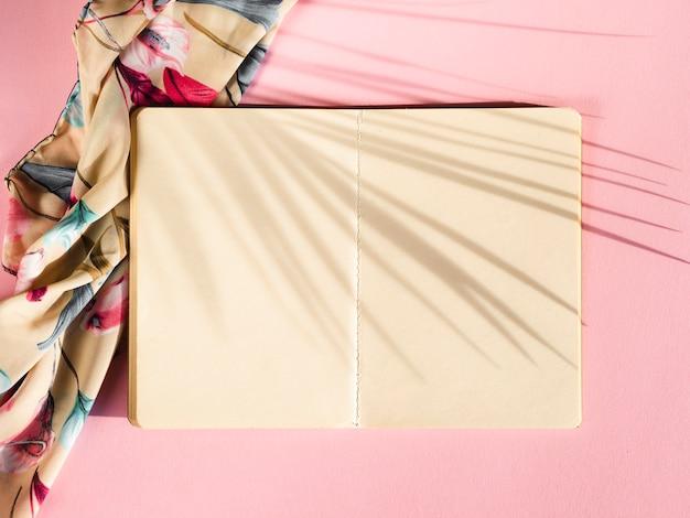 Cuaderno blanco sobre un fondo rosa con una sombra de hoja de palma