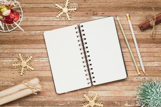 Cuaderno en blanco sobre madera con adornos navideños
