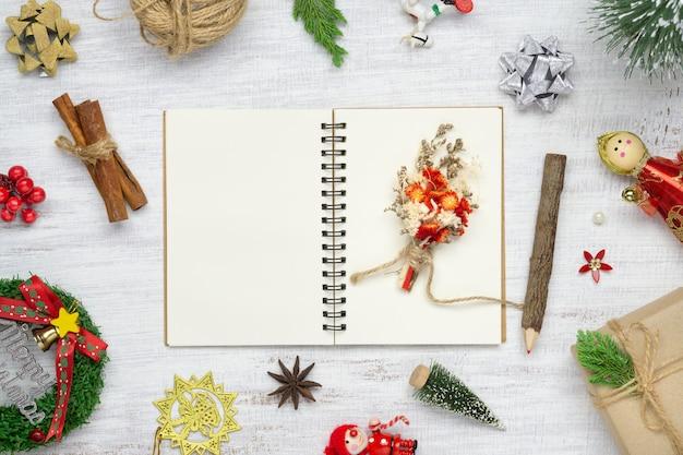 Cuaderno en blanco sobre madera blanca con adornos navideños.
