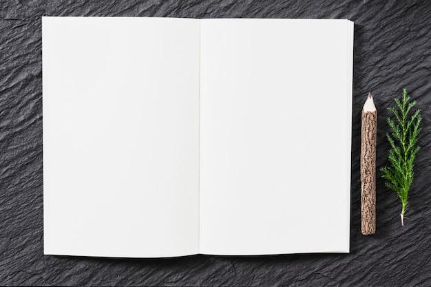Cuaderno en blanco sobre mesa con lápiz natural