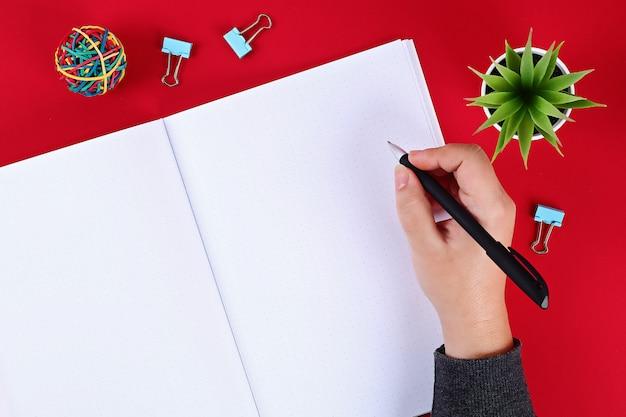 Cuaderno en blanco sobre una mesa roja