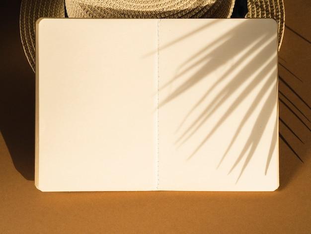 Cuaderno blanco sobre una sombra de sombrero y hoja de palma