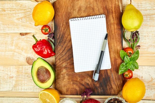Cuaderno en blanco sobre tabla para cortar con fruta