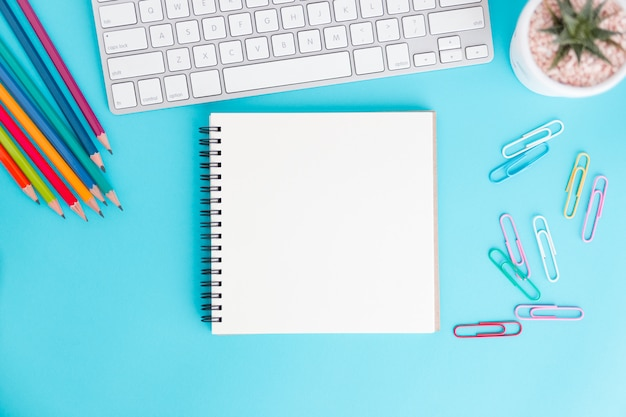 Cuaderno en blanco con teclado y lápiz en azul