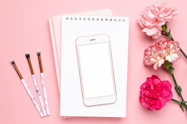 Cuaderno blanco y teléfono móvil con flor de clavel sobre un fondo rosa