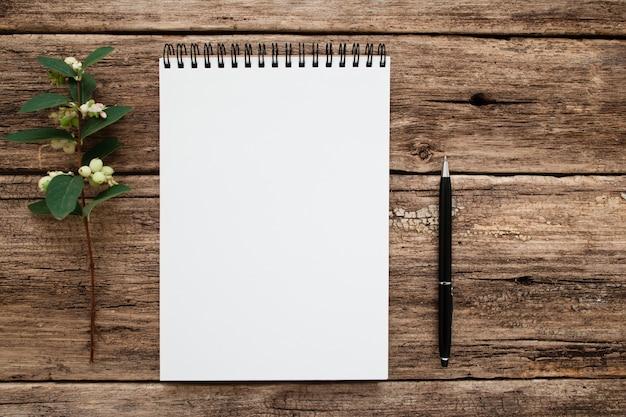 Cuaderno blanco vacío con flores y bolígrafo