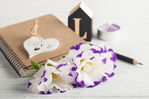 Cuaderno en blanco, velas, flores de eustoma