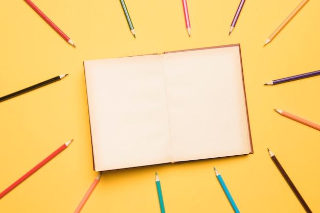 Cuaderno de bocetos abierto rodeado de lápices de diferentes colores.