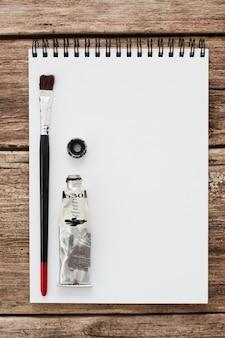 Cuaderno de bocetos en blanco con pincel y pintura negra