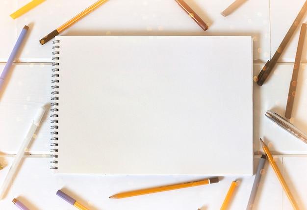 Cuaderno de bocetos y bolígrafos. un cuaderno y un montón de lápices.