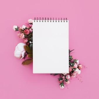 Cuaderno de bodas con hermosas flores sobre fondo rosa