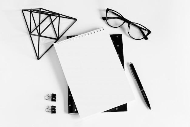 Cuaderno, bolígrafo, anteojos y hoja de papel blanco.