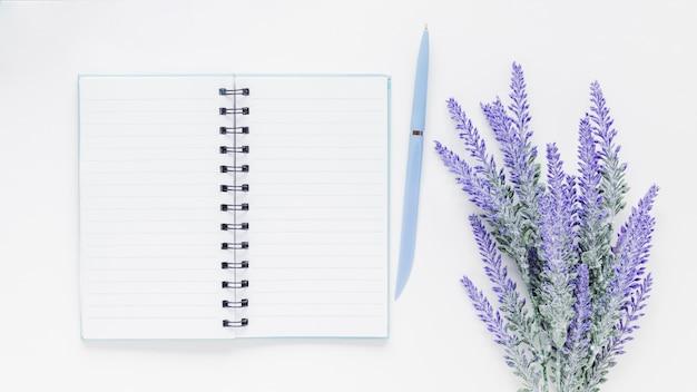 Cuaderno y bolígrafo cerca de flores de lavanda en el escritorio blanco