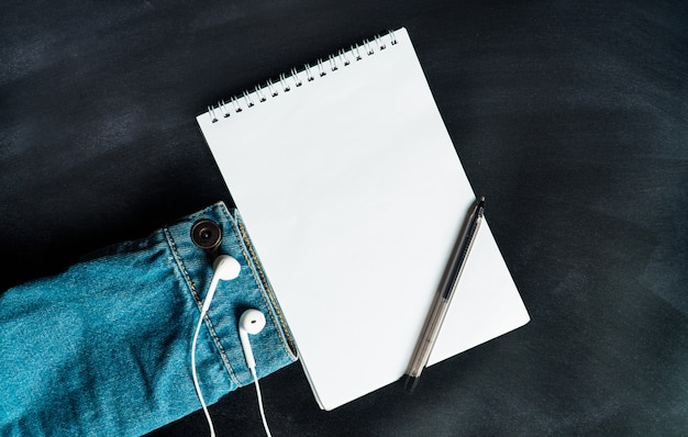 Cuaderno con bolígrafo, chaqueta y auriculares.