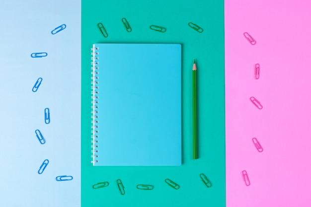 Cuaderno, bolígrafo, clip, sobre fondo azul pastel, verde, rosa. escritorio de oficina con espacio de copia. de vuelta a la escuela.
