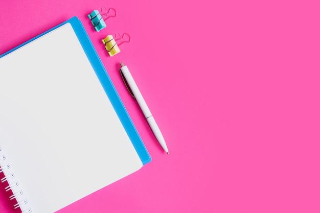 Cuaderno, bolígrafo, clips de papel sobre un fondo rosa