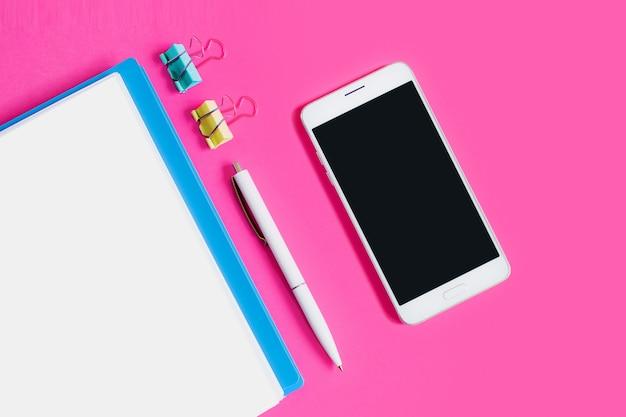 Cuaderno, bolígrafo, clips de papel, teléfono móvil sobre un fondo rosa