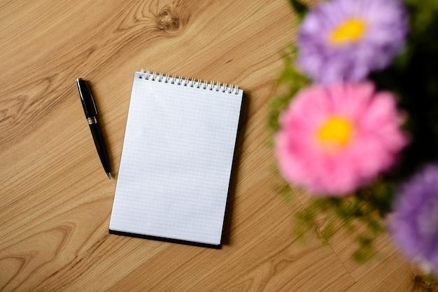 Cuaderno con bolígrafo y flores.