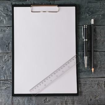 Cuaderno con bolígrafo, lápiz y regla sobre mesa de madera oscura.