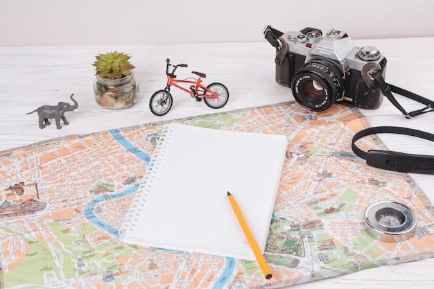 Cuaderno con bolígrafo en mapa cerca de animal de juguete, cámara y bicicleta