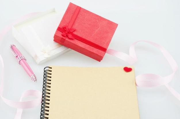 Cuaderno con bolígrafo rosa y cajas de regalo.