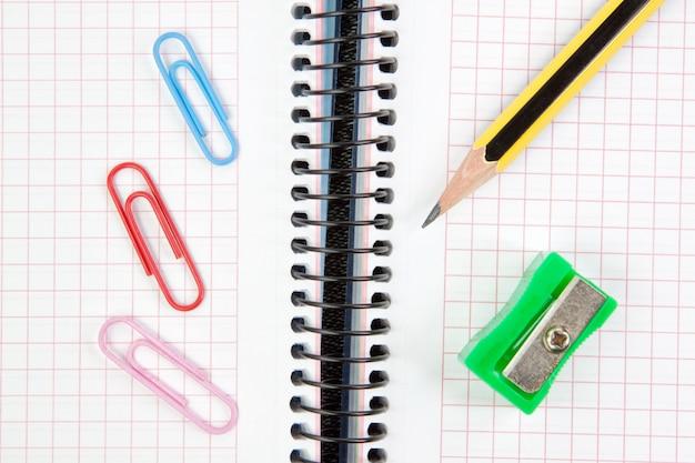 Cuaderno, bolígrafo, sacapuntas y clip de primer plano.