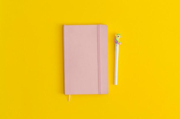 Cuaderno y bolígrafo sobre fondo amarillo. vista superior. endecha plana. concepto de regreso a la escuela.