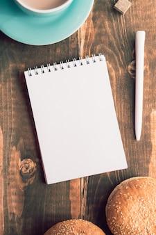 Cuaderno con un bolígrafo sobre la mesa junto al cacao