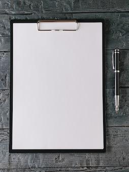 Cuaderno con bolígrafo sobre mesa de madera oscura