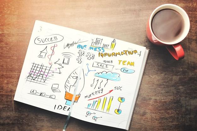 Cuaderno, bolígrafo y té en la mesa de madera