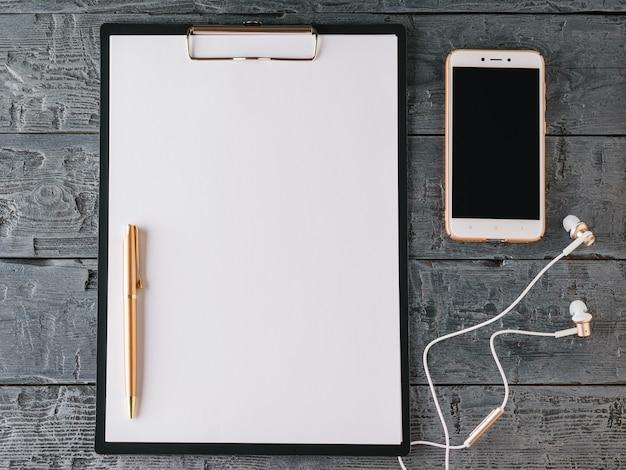 Cuaderno con bolígrafo, teléfono inteligente y auriculares en una mesa de madera oscura