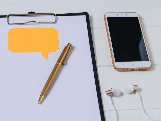 Cuaderno con bolígrafo, teléfono inteligente y auriculares en una mesa de madera