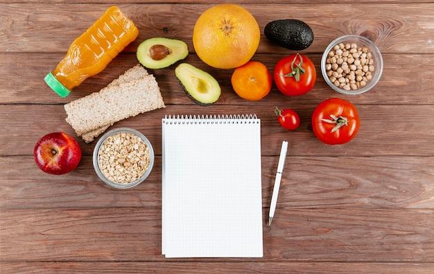 Cuaderno con bolígrafo y verduras
