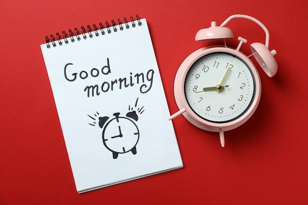 Cuaderno con buenos días y despertador en superficie roja