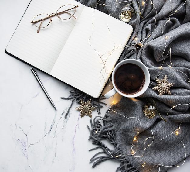 Cuaderno, bufanda, café y guirnalda.