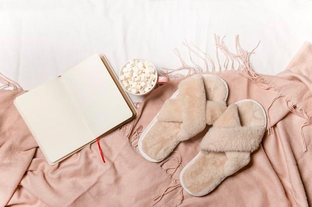 Un cuaderno y café con una manta caliente sobre la ropa de cama blanca desayuno en la cama
