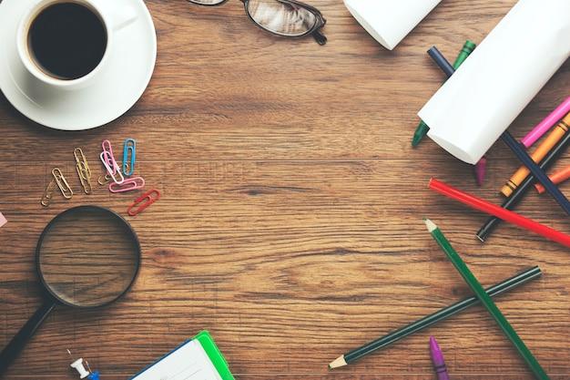 Cuaderno con café y muchos lápices de colores sobre mesa de madera