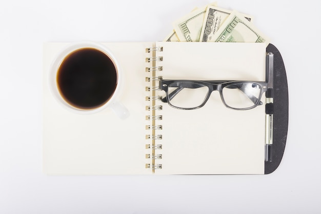 Cuaderno con café y vasos en el escritorio