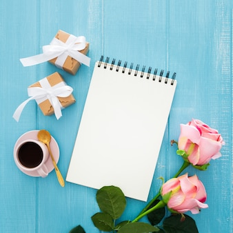 Cuaderno, cajas de regalo, café y rosas rosadas en madera azul