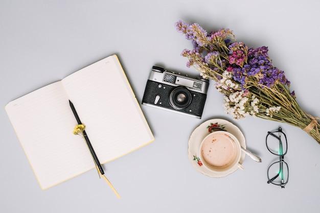 Cuaderno con camara y flores sobre mesa.