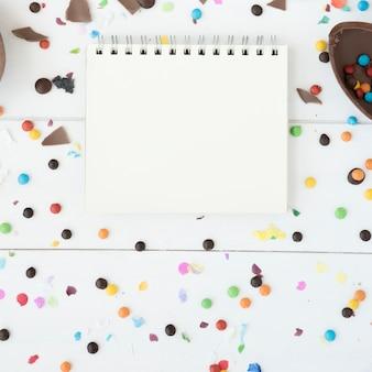 Cuaderno entre caramelos, huevo de chocolate y confeti.