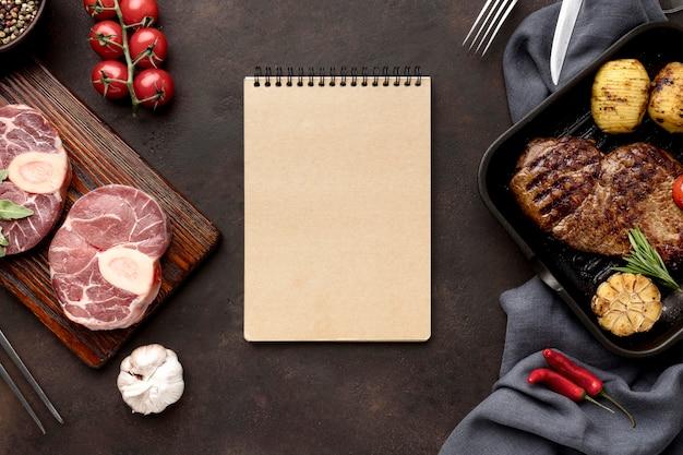 Cuaderno y carne preparada para cocinar