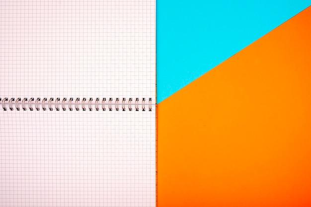 Cuaderno en el centro y hojas cuadradas sobre fondo azul y naranja