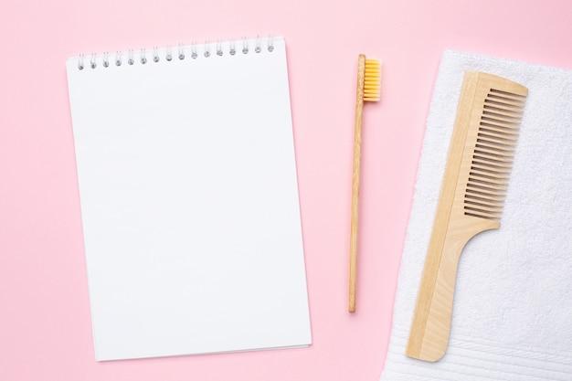 Cuaderno, cepillo de dientes de madera, peine y toalla de baño blanca sobre rosa