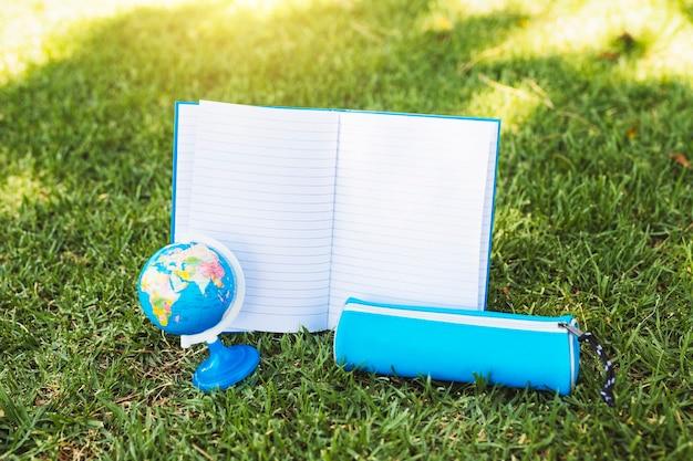 Cuaderno cerca de caja de lápices y globo sobre hierba