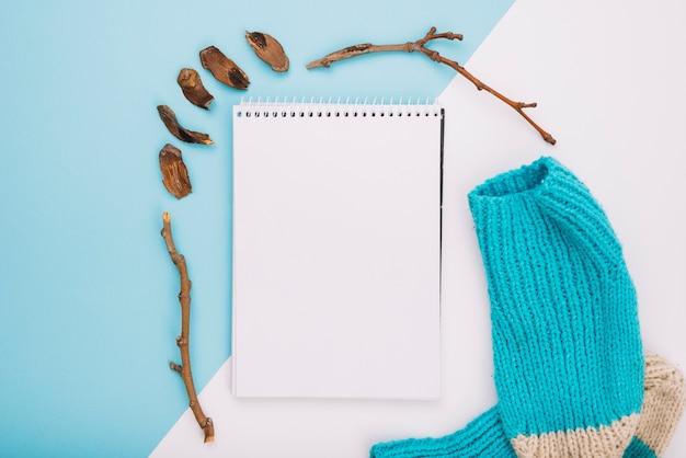 Cuaderno cerca de calcetines y ramitas.