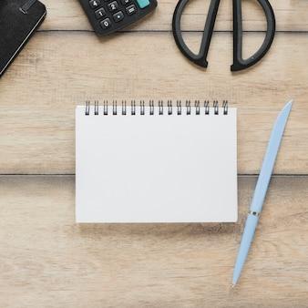 Cuaderno cerca de calculadora y tijeras en la mesa