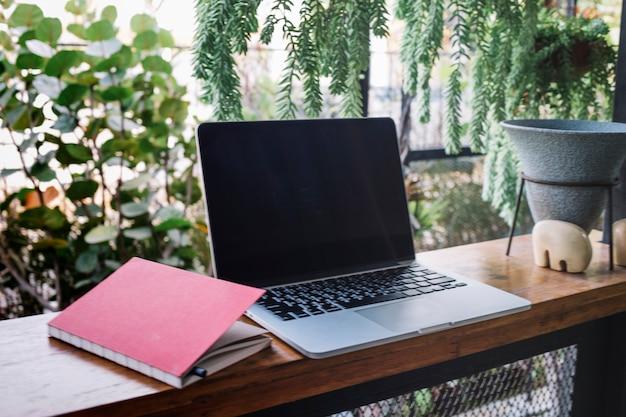 Cuaderno cerca de la computadora portátil en el jardín